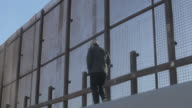 Man Walks Casually Along the US and Mexico Border Fence video