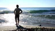 Man walks into sea shallows, looks out across water video
