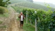 Man walks into vineyard, talking on smart phone video