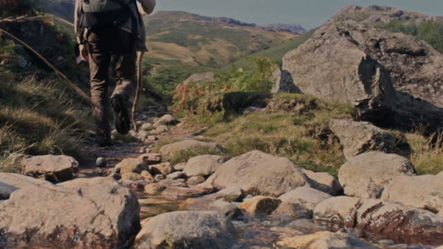 Man walks mountain trail away from camera video