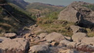 Man walks mountain trail toward camera slow motion video