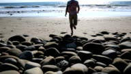 Man walks on shoreline rocks video