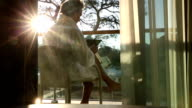 Man walks onto terrace with digital tablet, in bath robe video