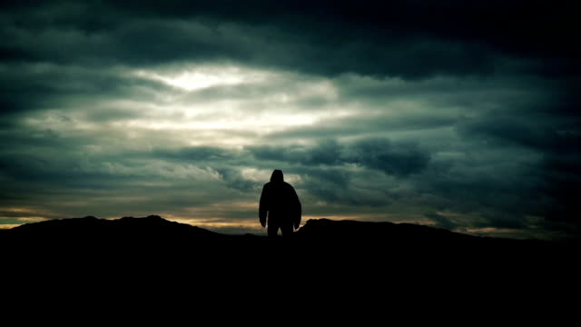 Man Walks Over Hill On Dramatic Sky Silhouette video