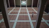 A man walks through a large room with columns and holding a phone video