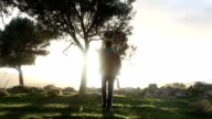 Man walks through forested glade towards sunrise video