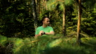 A man walks through the forest with smart watch and looking at the navigation application. He chooses the right direction video