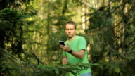 A man walks through the forest with the phone and looks at the navigation application. He chooses the right direction video