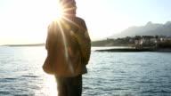 Man walks to sea edge, looks off, sunrise video