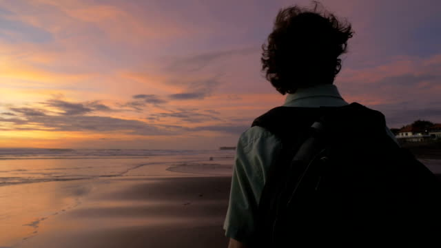 A man walks with a backpack on along the beach during sunset in slowmo video