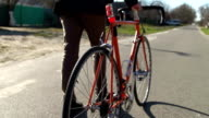 A man walks with a bicycle around the city. Slow motion video