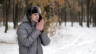 Man warms hands in winter video