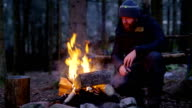 Man warms himself at camp fire in the woods video