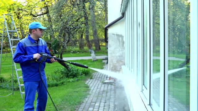man wash glass windows with water pressure jet. video