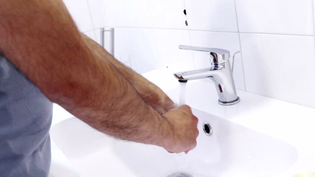 man wash his hands with water in the bathroom, care and body hygiene video