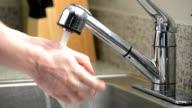 Man washes hands in kitchen sink video