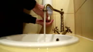 Man washes his hands in the sink, turns on rare valve, picks soap video
