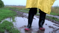 Man washes rubber boots in puddle on country road video