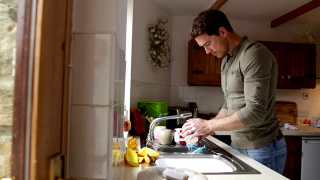 Man washing dishes in his home video