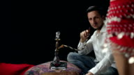 Man watching belly dance and smoking water pipe video