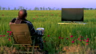 Man watching television in the green field video
