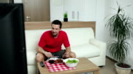 Man watching TV while having lunch video