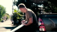 Man waxing surfboard in the back of his pickup truck video