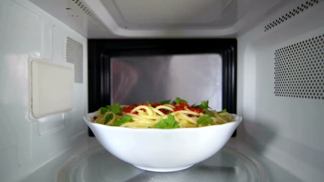 Man wearing a robe heating up cooked pasta dish in the microwave oven video