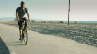 Man Wearing Artificial Leg Riding Bike on Beach video