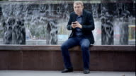 Man Wearing Suit Sitting Near Fountain Writing Sms On His Phone video