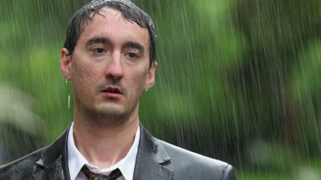 Man wearing suit standing in rain video