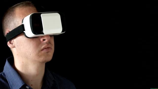 Man wearing virtual reality goggles. Studio shot, black background.slow motion video