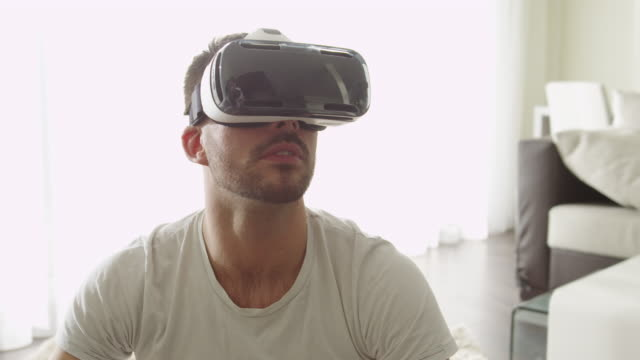Man Wearing VR Headset and Playing Games with Controller at Living Room. video