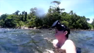 Man wearing VR headset 'looks around' at tropical island environment as he stands in tropical lagooon video