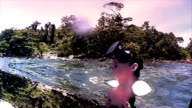 Man wearing VR virtual headset in ocean lagoon looks around in wonder  (effects added) video