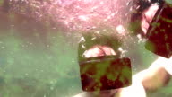 Man wearing VR virtual reality headset underwater starts normal, then turns surreal as he submerges underwater video