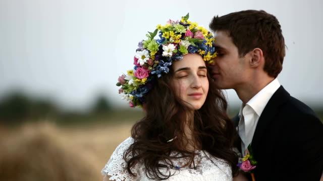 Man wears a wreath flowers on head of girl. video