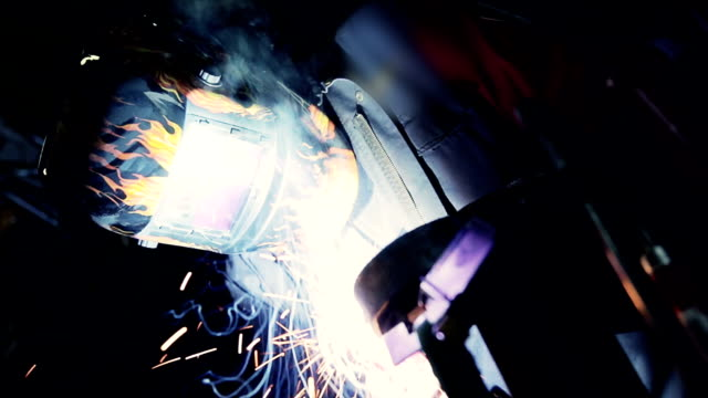 Man welds the metal with helmet  and sparks video