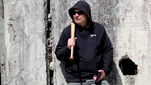Man with a baseball bat watching near wall video