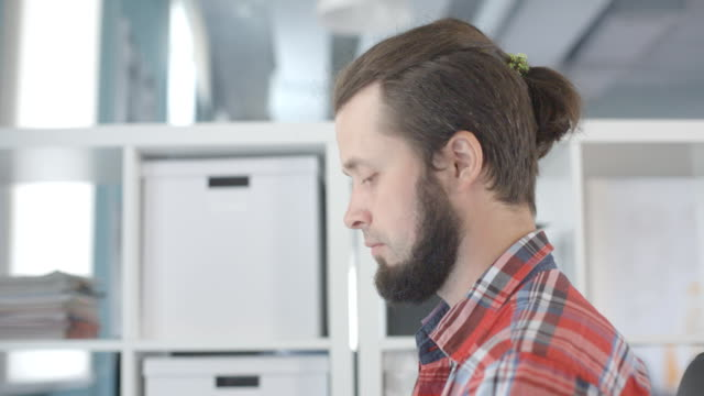 A man with a beard and a tuft of hair on head, works in office video