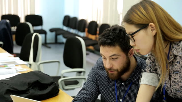 A man with a beard and a woman of asian appearance with glasses work together in office video
