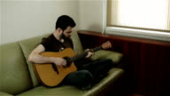 A man with a beard sitting cross-legged playing the guitar. video