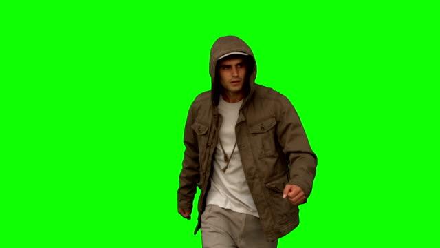 Man with a coat walking toward camera on green screen video