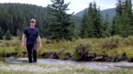 A man with a fishing rod walks past the camera away from a river video