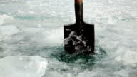 Man with a shovel chop a hole in the ice video