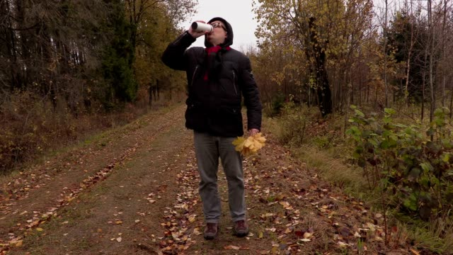 Man with autumn leaves holding cup with drink and walking video