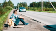 Man with backpack sit at road in countryside. Hitchhiking. Waiting. Smartphone video