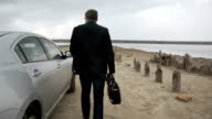 Man With Bag Walking Near Car In The Countryside In Slowmotion video
