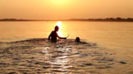 man with beagle puppy fooling around in ocean sunset waves video