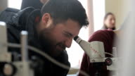 Man with beard looking into optical microscope screwing up his one eye video